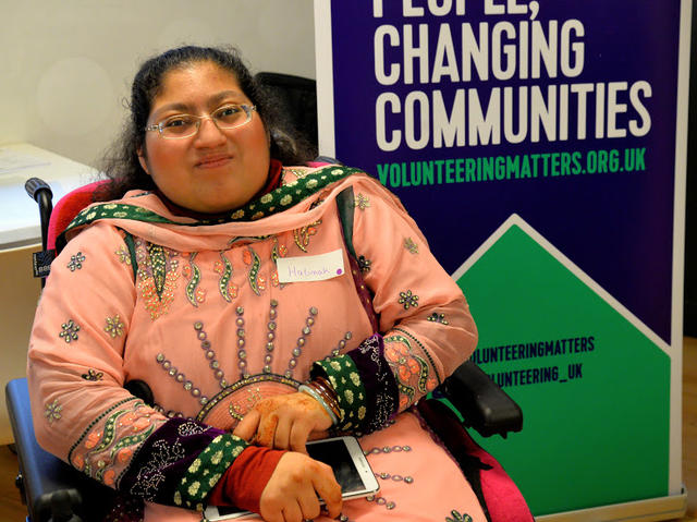 Halimah next to Volunteering Matters display banner
